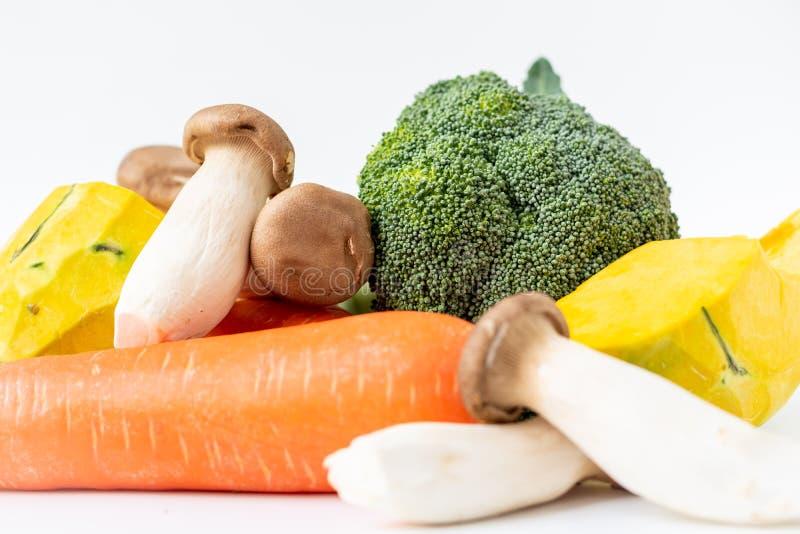 Grupo de bróculi, de zanahoria, de seta y de diapositiva frescos de la calabaza en el fondo blanco imagen de archivo