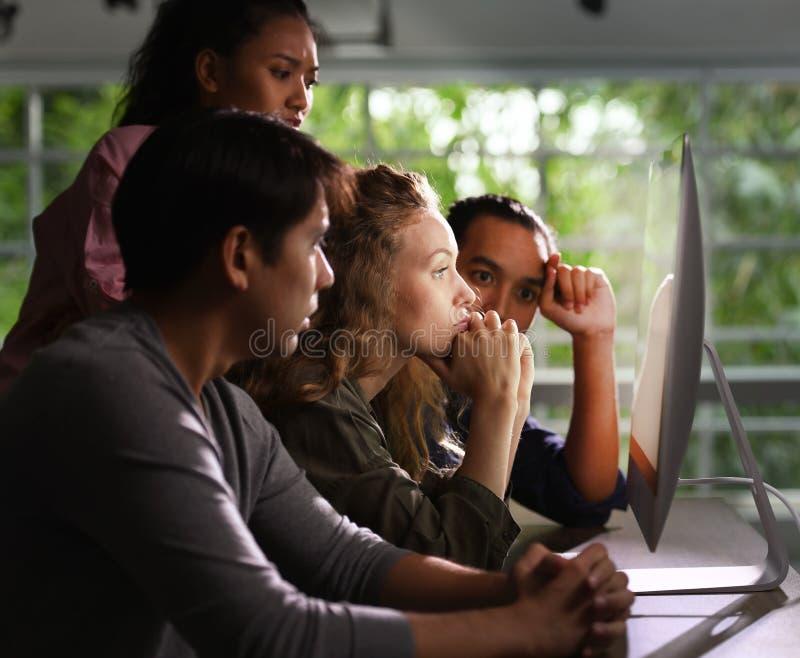 Grupo de businesspersons jovenes que miran atento la pantalla fotografía de archivo