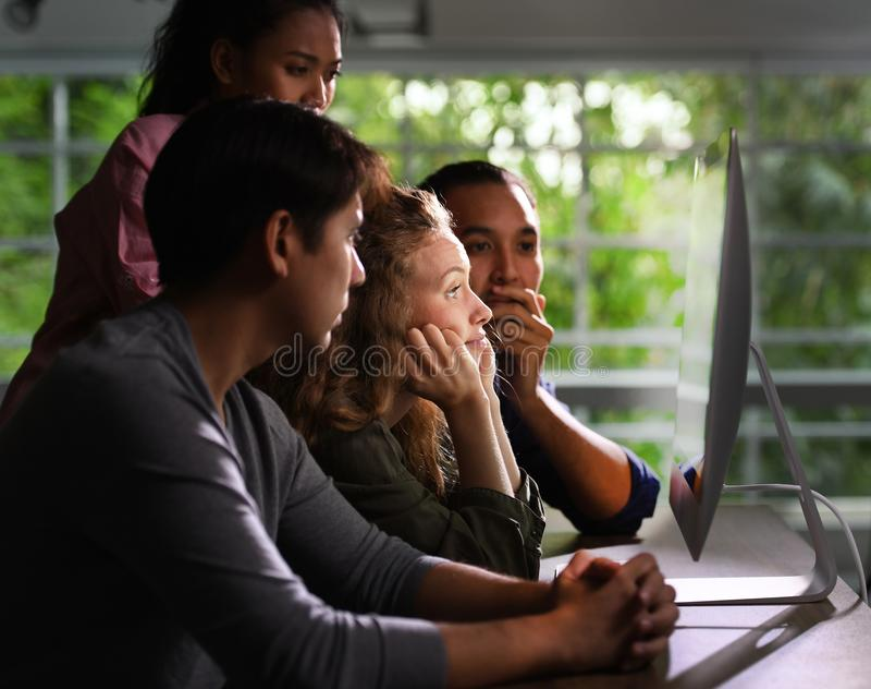 Grupo de businesspersons jovenes que miran atento la pantalla fotos de archivo libres de regalías