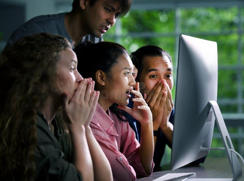 Grupo de businesspersons jovenes que miran atento la pantalla fotografía de archivo libre de regalías