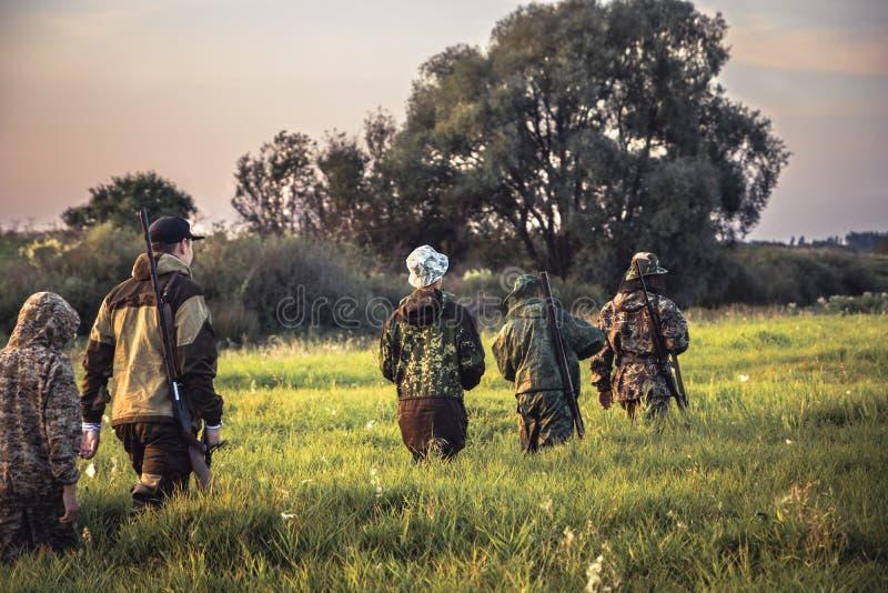 Grupo de caçadores dos homens que atravessam a grama alta no campo rural no por do sol durante a época de caça fotos de stock royalty free