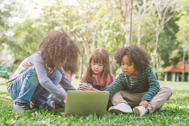 Grupo de cabritos con la computadora portátil niños felices en naturaleza con el grupo de amigo imagenes de archivo