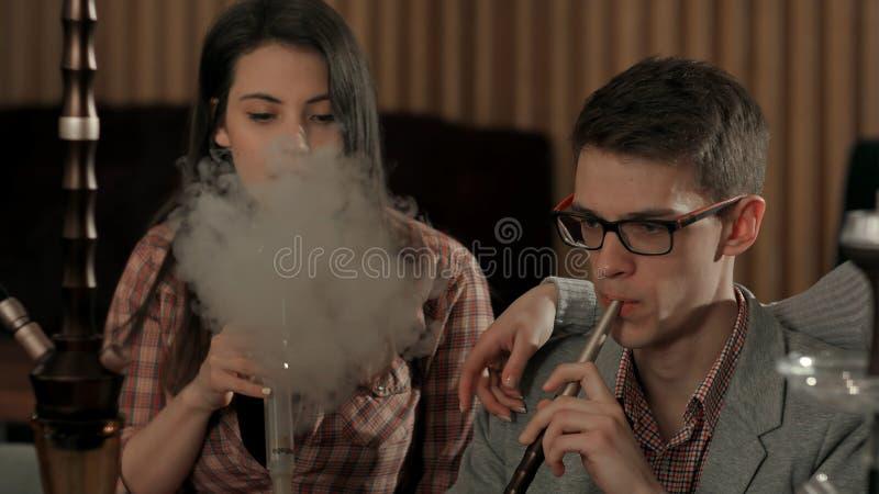 Grupo de cachimba que fuma de la gente joven en el caffee del salón foto de archivo