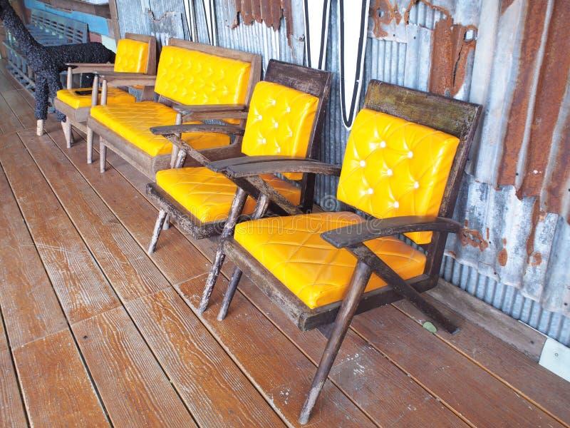 Grupo de cadeiras de madeira velhas do vintage com o coxim amarelo sobre rústico imagem de stock royalty free