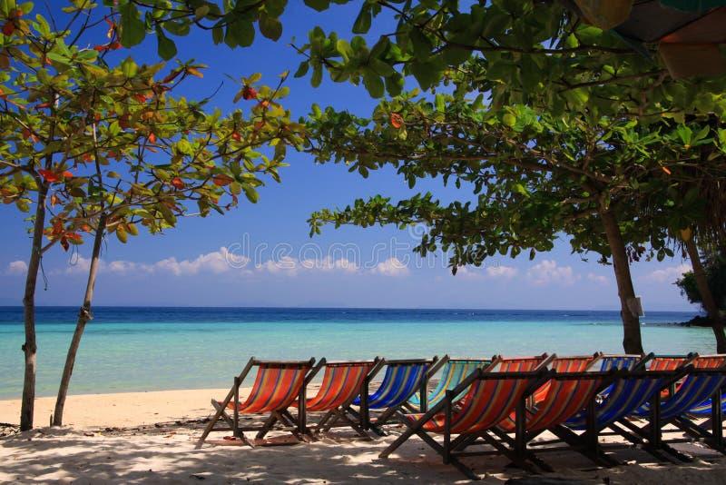 Grupo de cadeiras de plataforma vazias isoladas na praia da ilha tropical com vista panorâmica na água de turquesa foto de stock royalty free