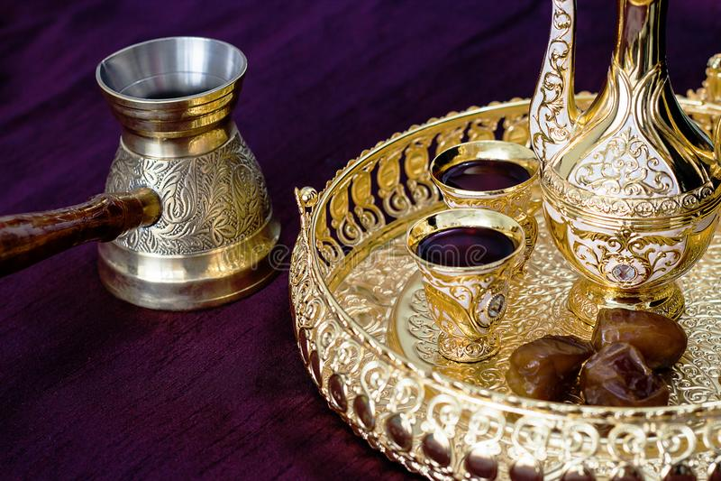 Grupo de café árabe tradicional dourado com dallah, jezva do potenciômetro do café, copo e datas Fundo escuro fotos de stock