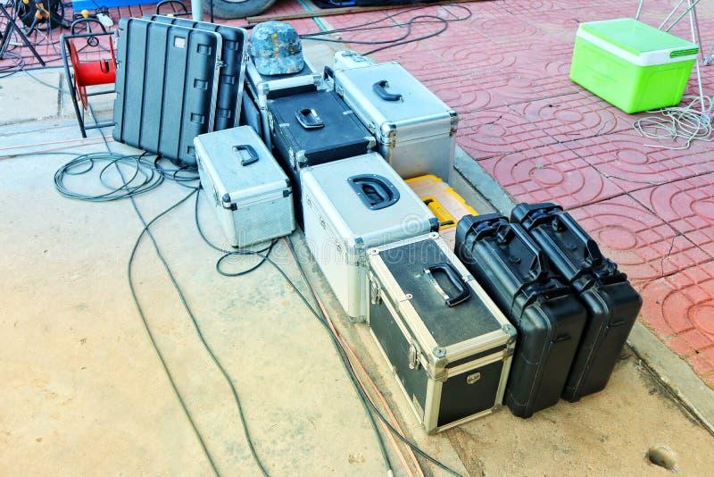 Grupo de caixas de aço inoxidável, couro, sacos de plástico colocados no assoalho do cimento fotografia de stock