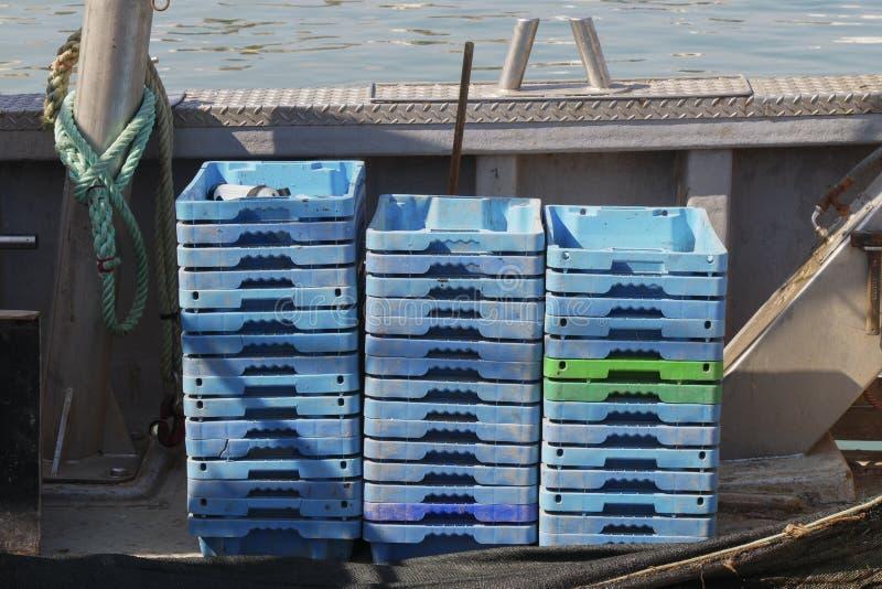 Grupo de cajas plásticas listas para ser llenado de los pescados frescos en una nave pesquera imagen de archivo