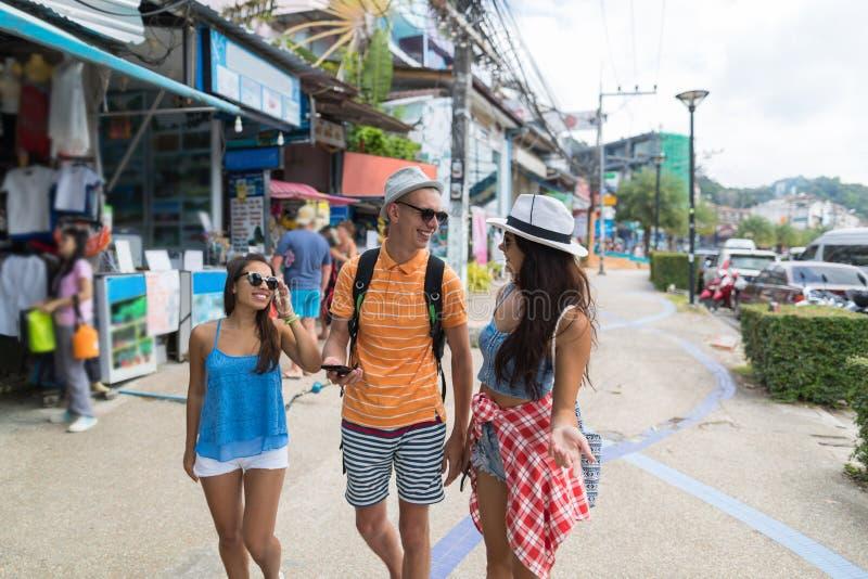 Grupo de calle que camina de los turistas de la ciudad asiática junto que busca la dirección correcta en teléfono móvil fotos de archivo