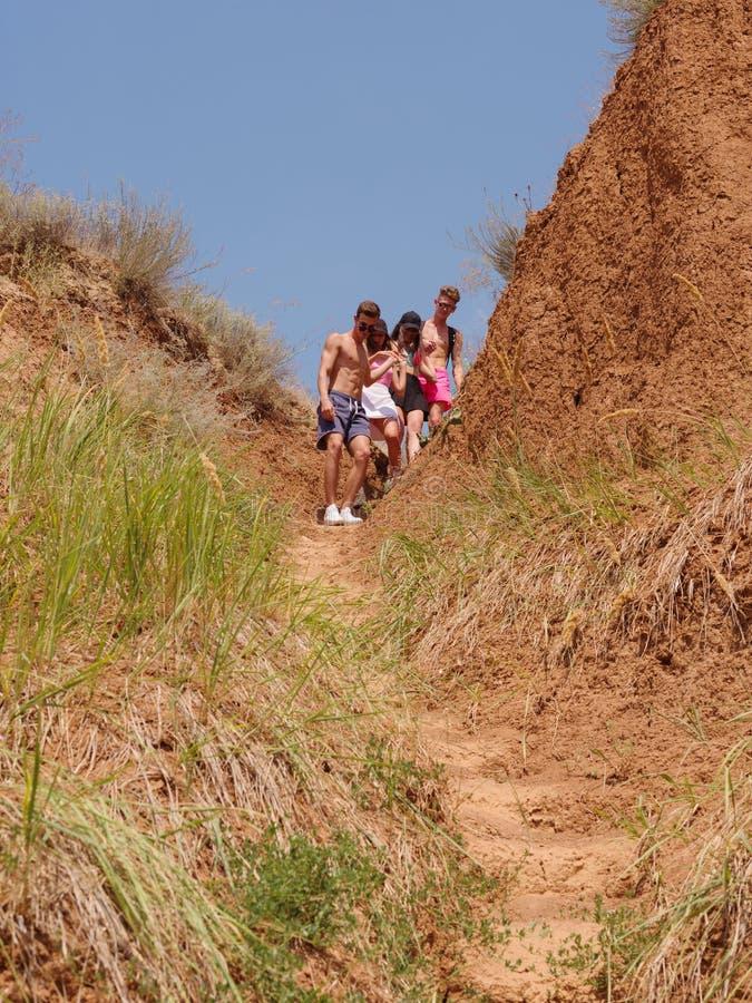 Grupo de caminantes en una montaña Mujer que ayuda a su amigo a subir una roca Gente joven en alza de la montaña en la puesta del fotografía de archivo libre de regalías
