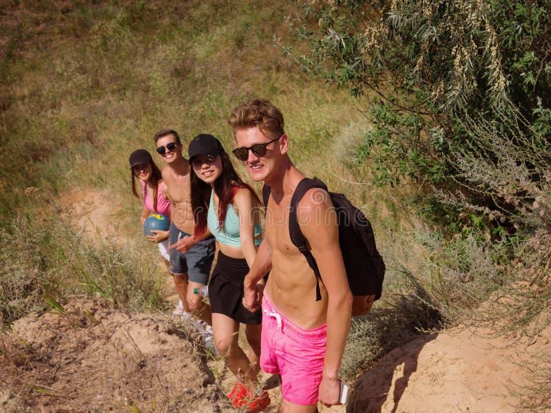 Grupo de caminantes en una montaña Mujer que ayuda a su amigo a subir una roca Gente joven en alza de la montaña en la puesta del foto de archivo libre de regalías