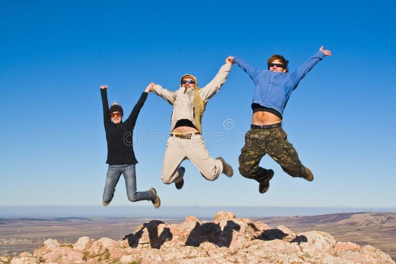 Grupo de caminantes que saltan en cumbre de la montaña fotos de archivo libres de regalías