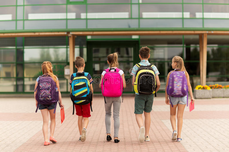 Grupo de caminar feliz de los estudiantes de la escuela primaria imagen de archivo