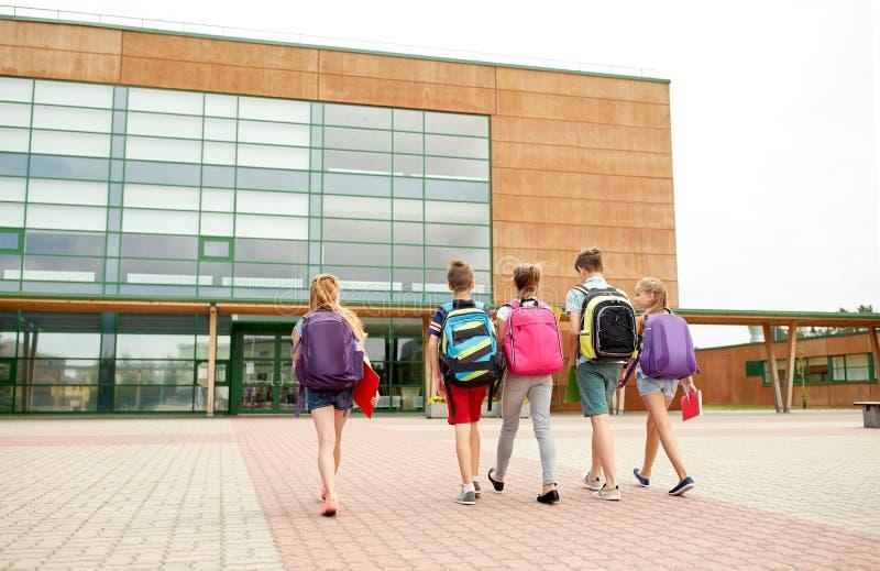 Grupo de caminar feliz de los estudiantes de la escuela primaria fotos de archivo
