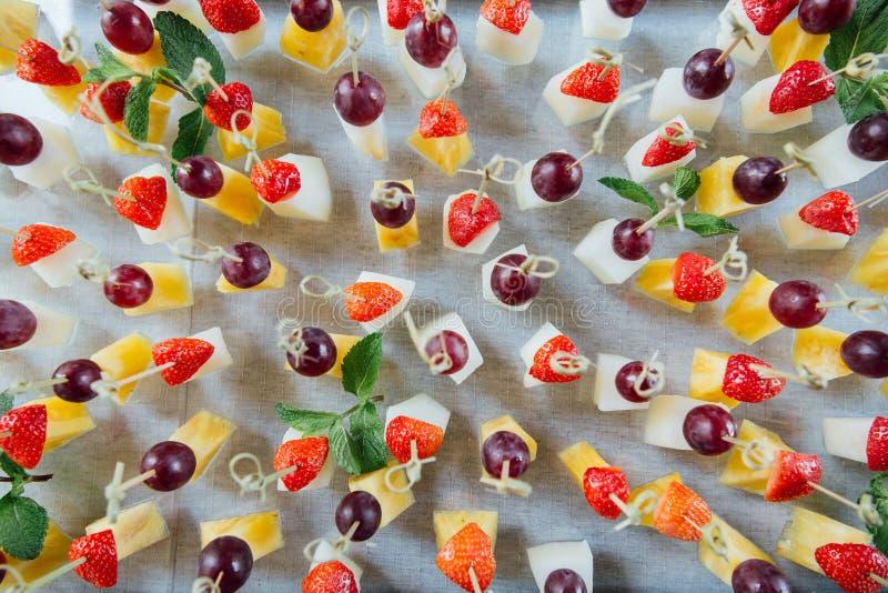 Grupo de canapes deliciosos com morango, abacaxi, melão e uva fotos de stock royalty free