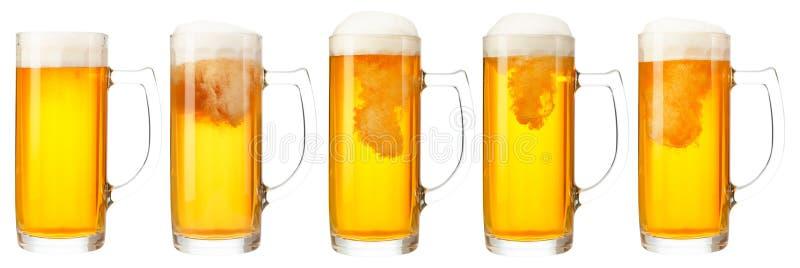 Grupo de canecas de cerveja clara fria com a espuma isolada no fundo branco fotografia de stock royalty free