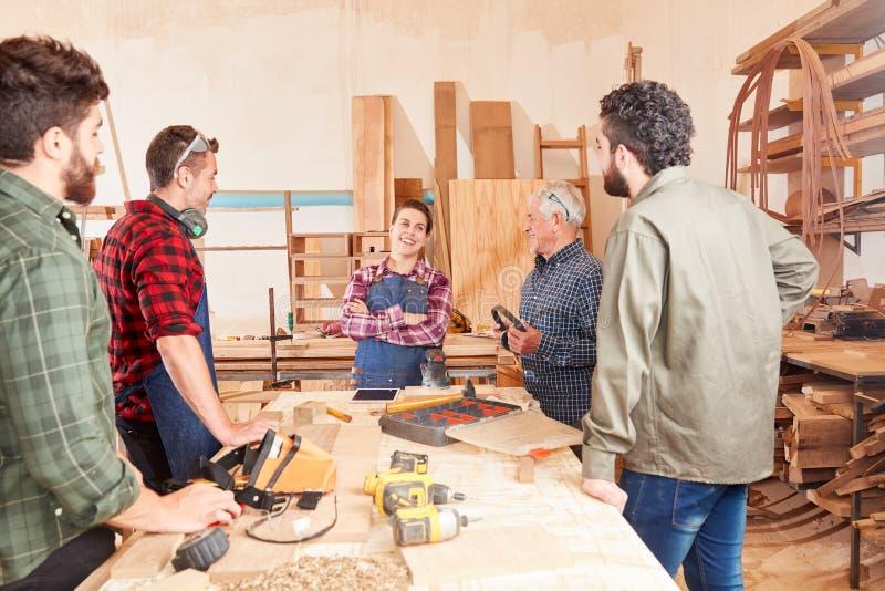 Grupo de carpinteros con los aprendices en el taller imagen de archivo libre de regalías