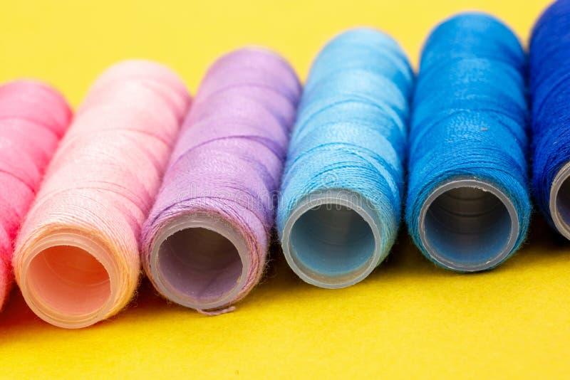 Grupo de carretes coloridos del hilo usados a la costura, a la costura y al bordado sobre fondo amarillo brillante imágenes de archivo libres de regalías