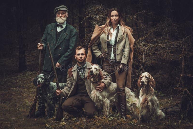 Grupo de cazadores de la multi-edad con los perros y las escopetas en una ropa tradicional del tiroteo, presentando en un fondo o foto de archivo
