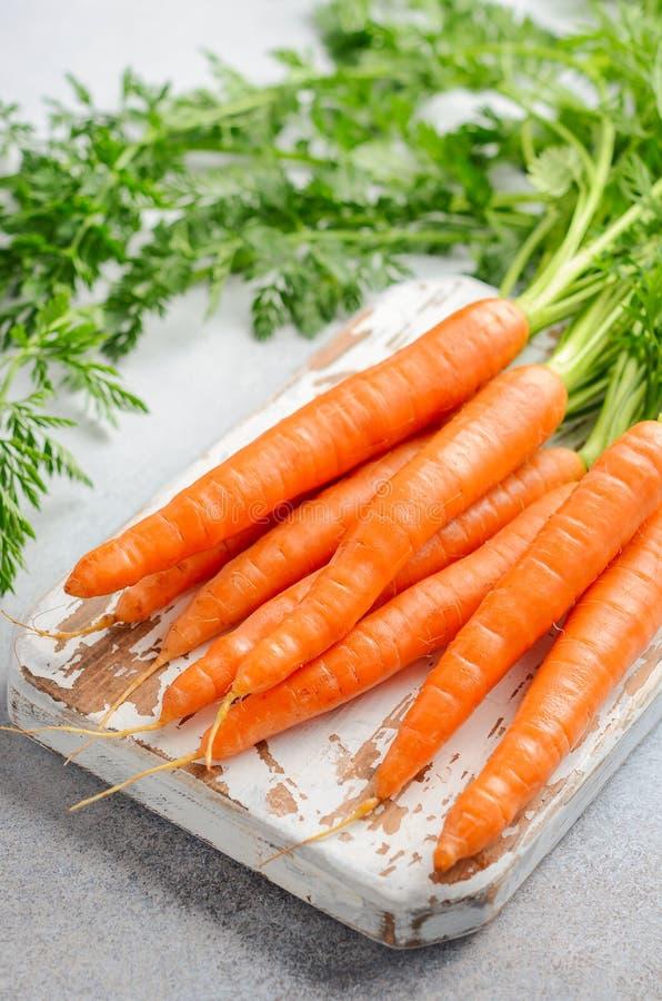 Grupo de cenouras frescas na placa de corte de madeira imagens de stock royalty free