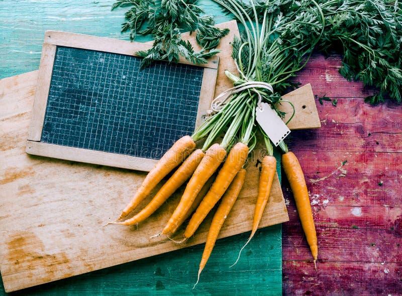 Grupo de cenouras frescas na placa de corte de madeira imagens de stock