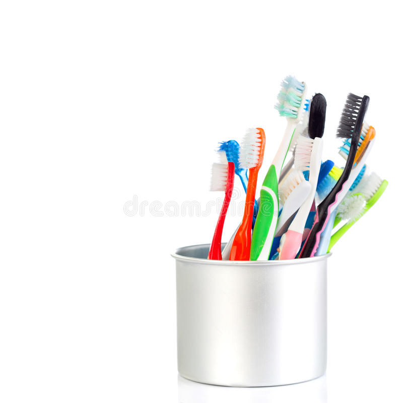 Grupo de cepillo de dientes viejo y usado en taza del metal foto de archivo
