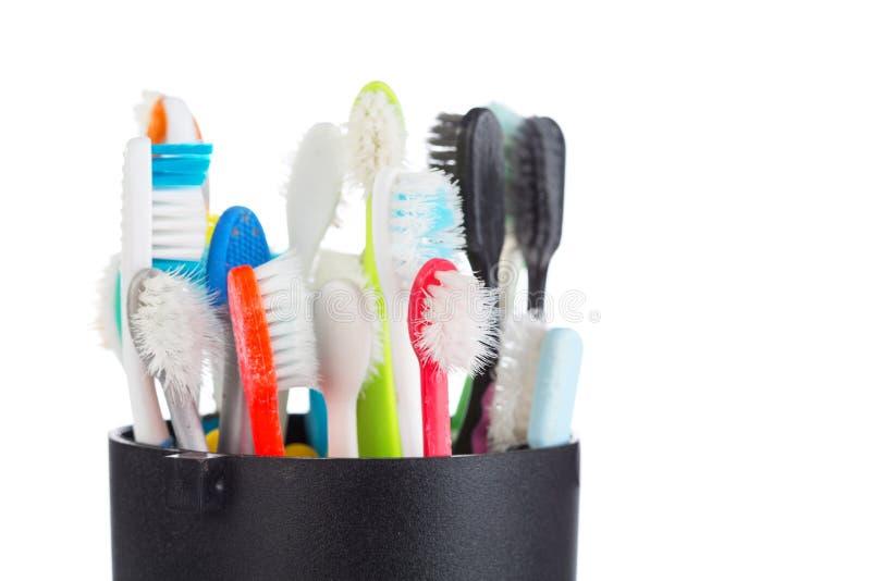 Grupo de cepillo de dientes viejo y usado en taza plástica fotografía de archivo libre de regalías