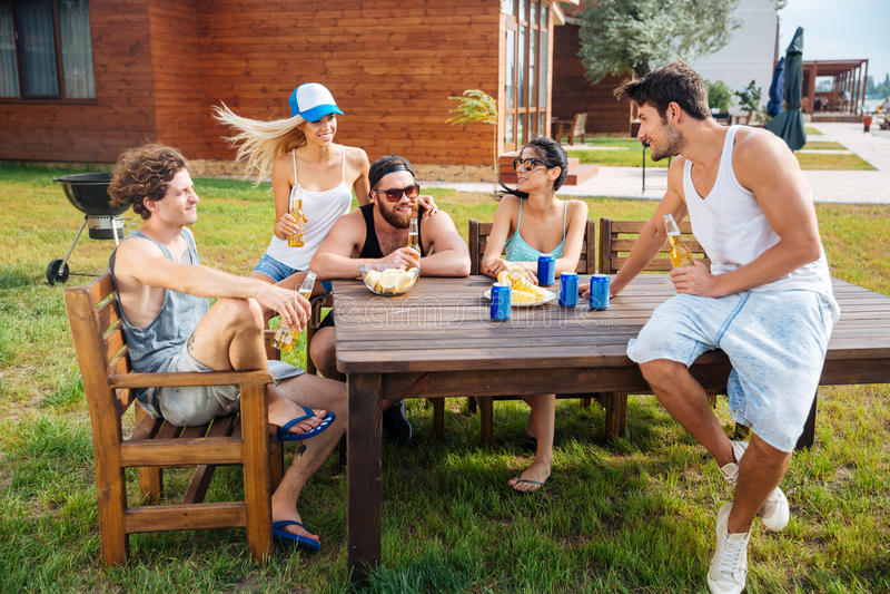 Grupo de cerveja de assento e bebendo feliz dos jovens fora fotografia de stock