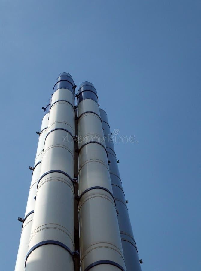 Grupo de chaminés industriais de aço modernas altas que estão contra um céu azul brilhante e umas nuvens brancas fotografia de stock