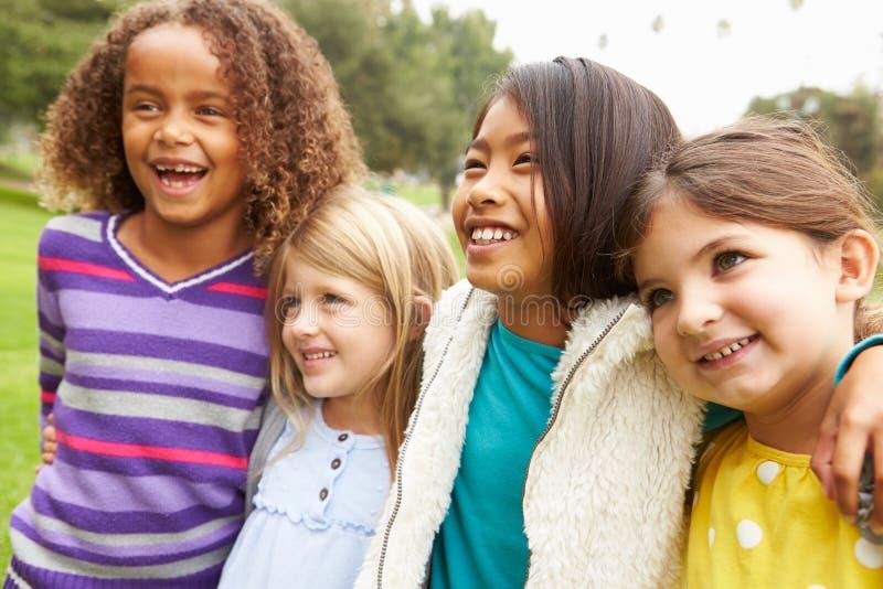 Grupo de chicas jóvenes que cuelgan hacia fuera en parque junto fotos de archivo libres de regalías