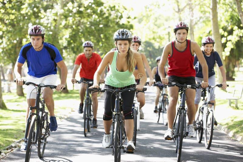 Grupo de ciclistas en paseo del ciclo a través del parque fotos de archivo