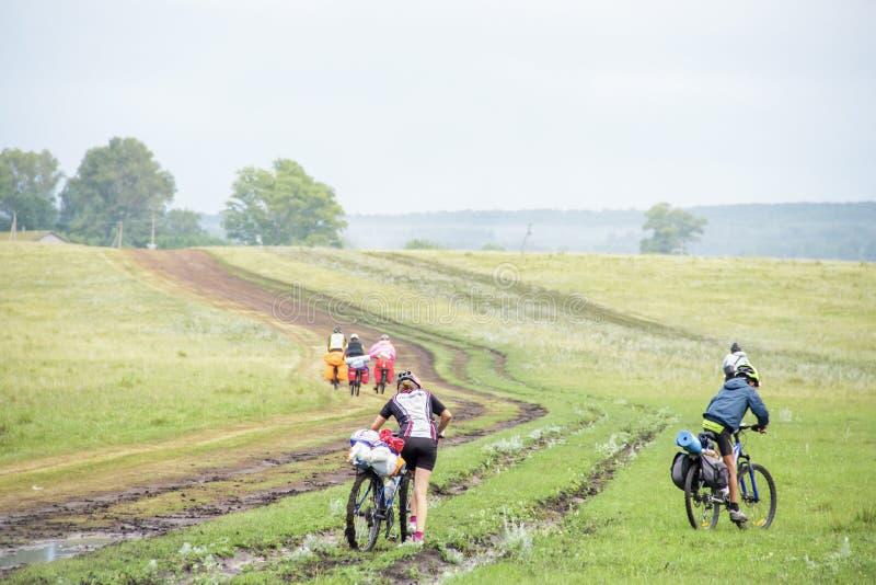 Grupo de ciclistas en paseos de la bici de los deportes con las mochilas a lo largo de un camino de tierra a través de un valle fotografía de archivo
