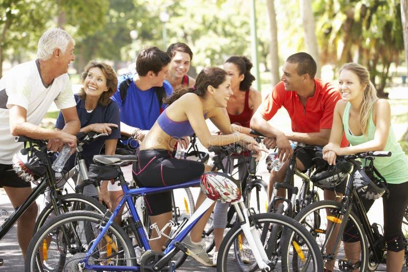 Grupo de ciclistas que descansam durante o passeio do ciclo através do parque imagens de stock