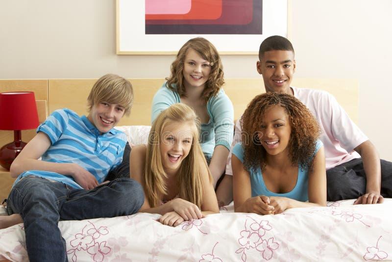 Grupo de cinco amigos adolescentes que penduram para fora em Bedro fotografia de stock