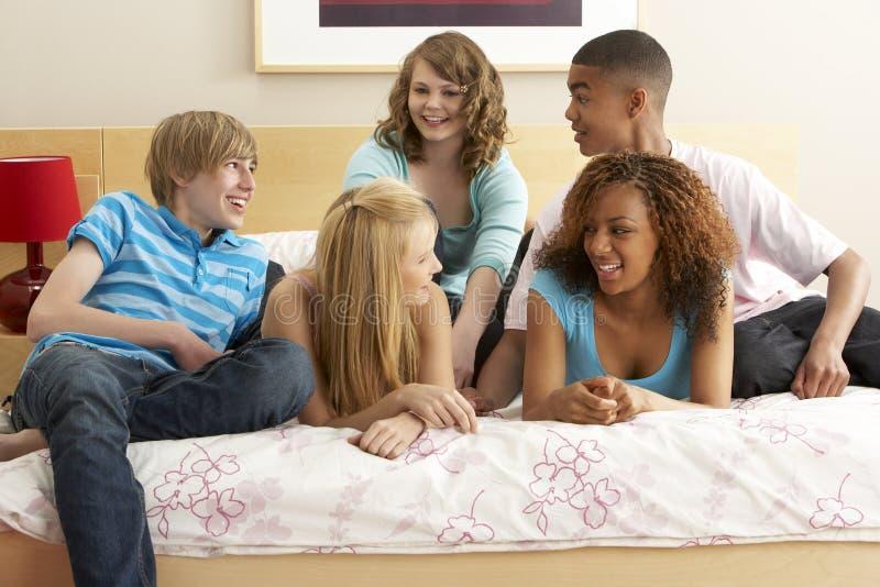 Grupo de cinco amigos adolescentes que penduram para fora em Bedro fotos de stock