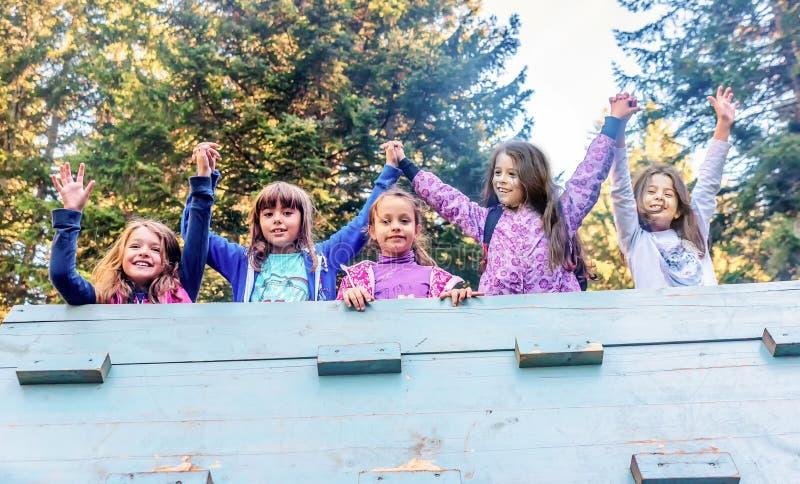Grupo de cinco amigos fêmeas da escola que guardam as mãos no playgro imagens de stock