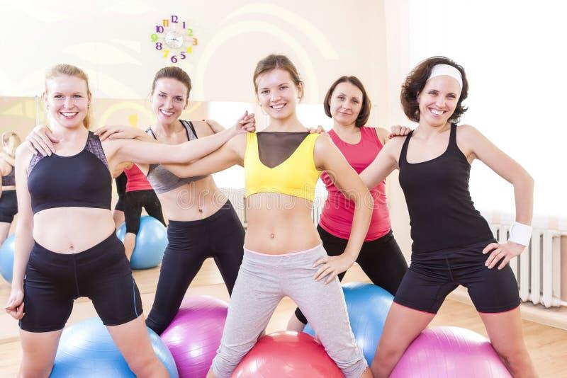 Grupo de cinco atletas de sexo femenino caucásicos felices que presentan juntos abrazado contra Fitballs foto de archivo libre de regalías