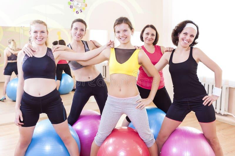 Grupo de cinco atletas de sexo femenino caucásicos felices que presentan juntos abrazado contra Fitballs imagenes de archivo