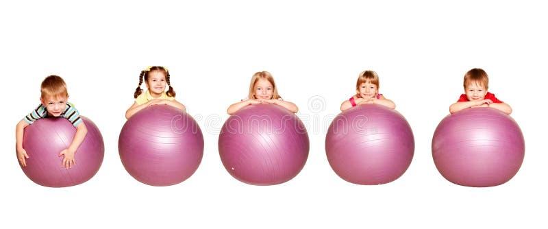 Grupo de cinco crianças que jogam esportes fotos de stock