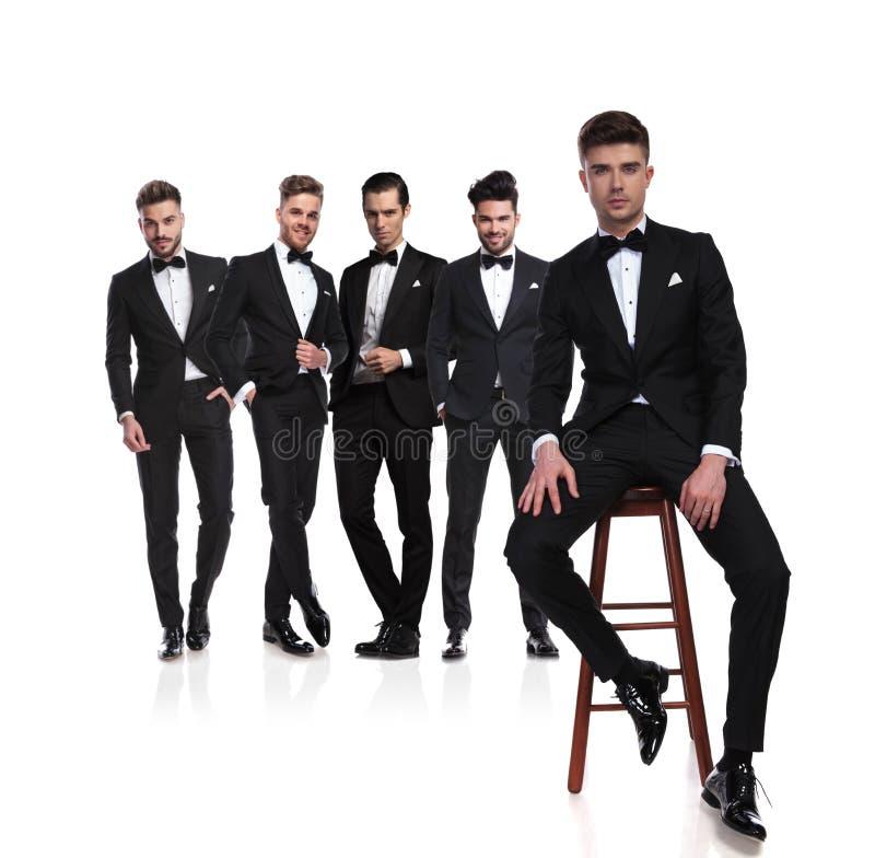 Grupo de cinco hombres elegantes con el líder que se sienta en silla imagenes de archivo