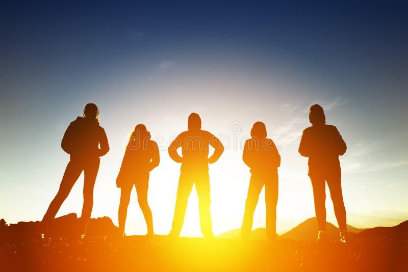 Grupo de cinco povos nas silhuetas no por do sol imagem de stock royalty free