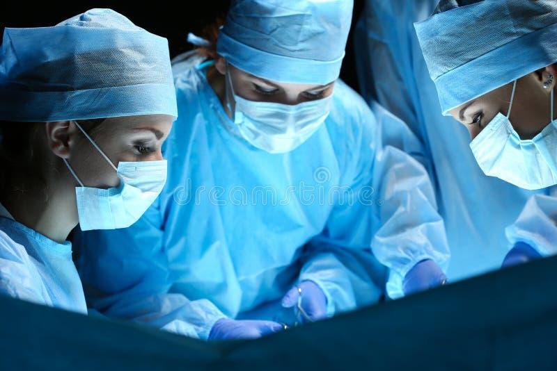 Grupo de cirurgiões no trabalho que opera-se no teatro cirúrgico fotografia de stock royalty free