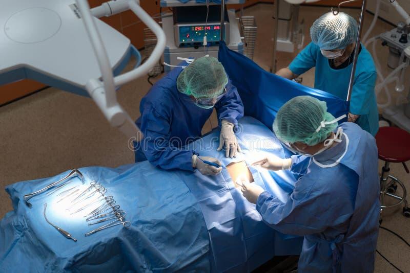 Grupo de cirurgi?es no trabalho no teatro de funcionamento Equipa m?dica que executa a opera??o imagem de stock