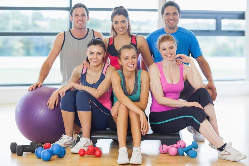 Grupo de clase de la aptitud en una sala de ejercicio brillante fotos de archivo