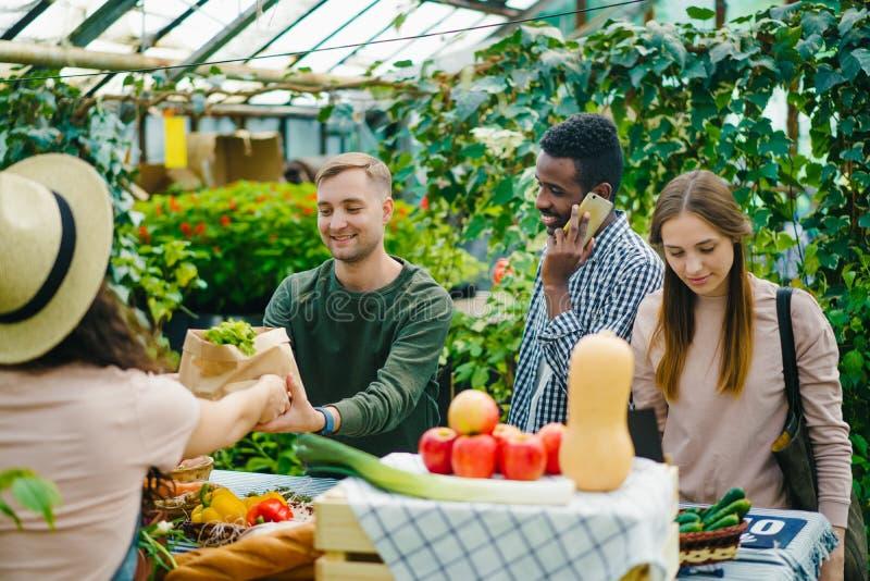Grupo de clientes que eligen comida orgánica en el mercado hablando con la vendedora fotos de archivo