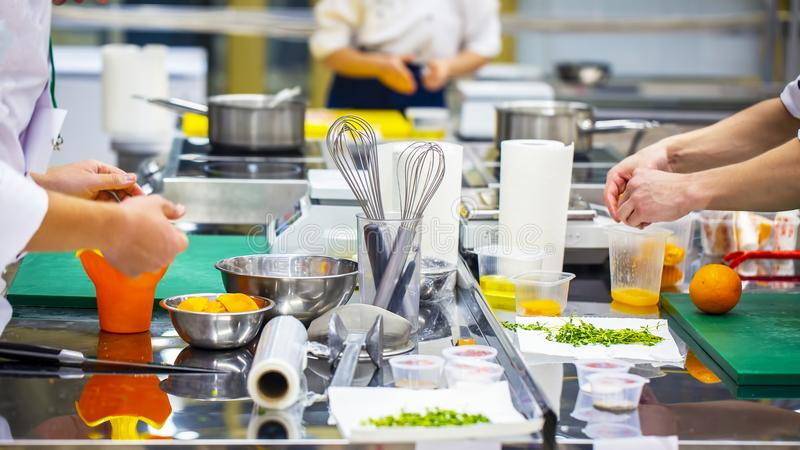 Grupo de cocinero que prepara la comida en la cocina de un restaurante fotografía de archivo