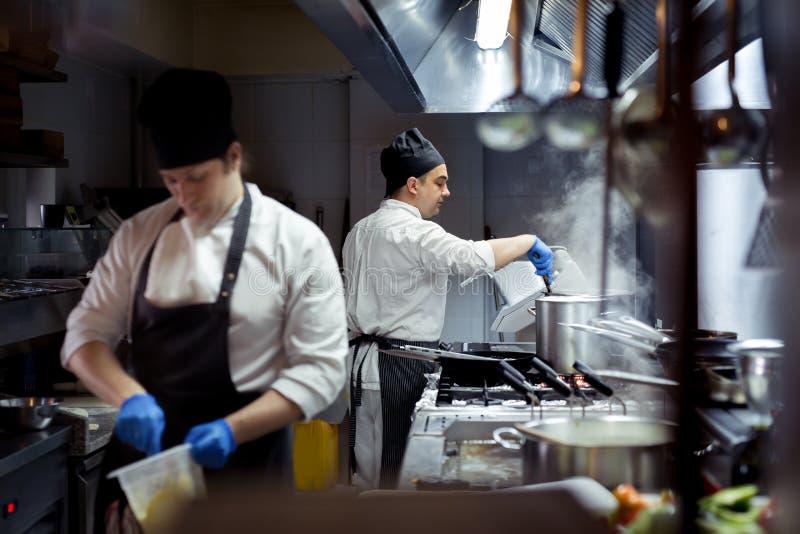 Grupo de cocinero que prepara la comida en la cocina de un restaurante imágenes de archivo libres de regalías