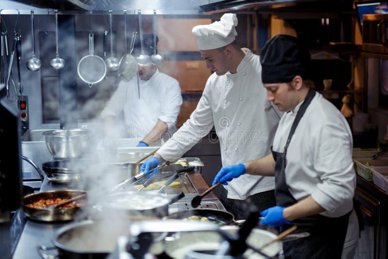 Grupo de cocineros que trabajan en la cocina fotos de archivo