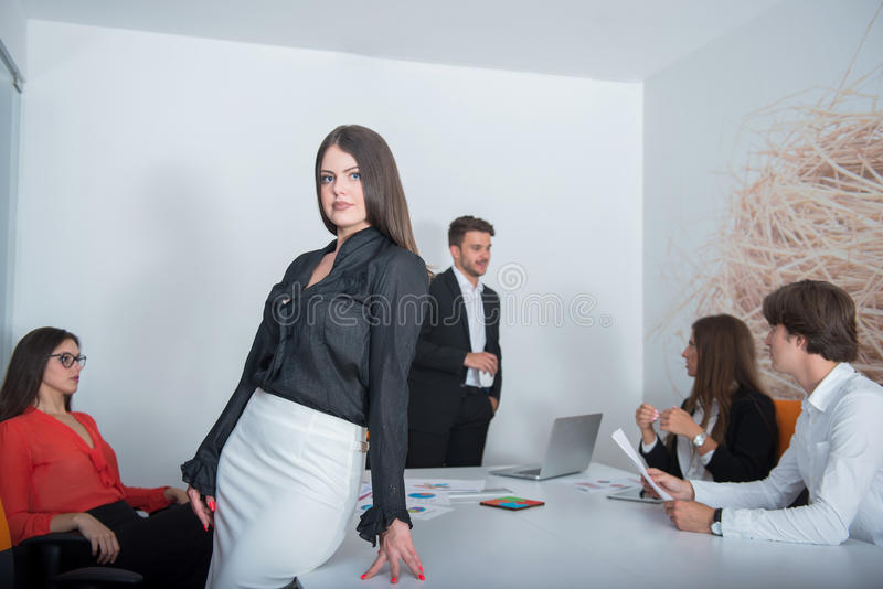 Grupo de colegas do negócio que escutam um homem de negócios durante uma reunião imagem de stock royalty free