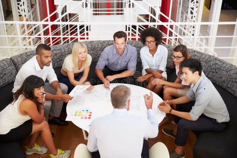 Grupo de colegas do trabalho que têm a reunião em uma entrada do escritório imagem de stock royalty free